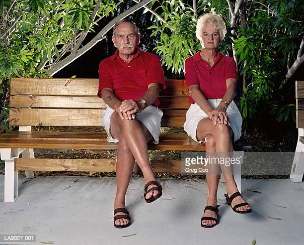 Mature couple in matching clothes on garden bench, portrait