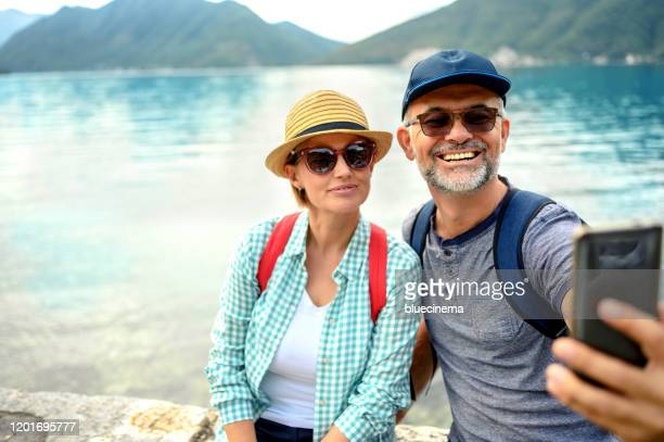 mature couple in nature taking photo with smart phone - kotor bay stock pictures, royalty-free photos & images