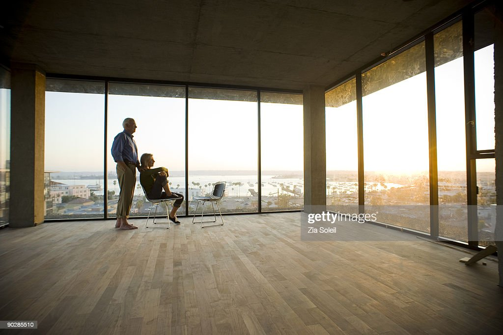 mature couple in new condo, sunset : Bildbanksbilder