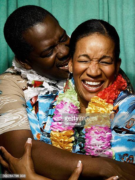 Mature couple in photo booth, man biting woman's ear