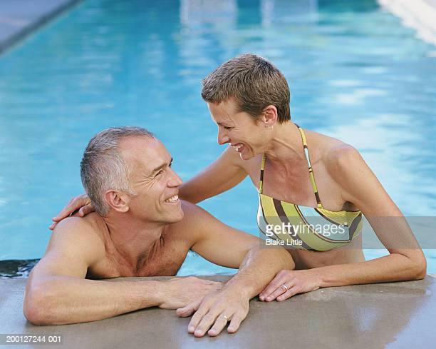 Mature couple in pool, smiling