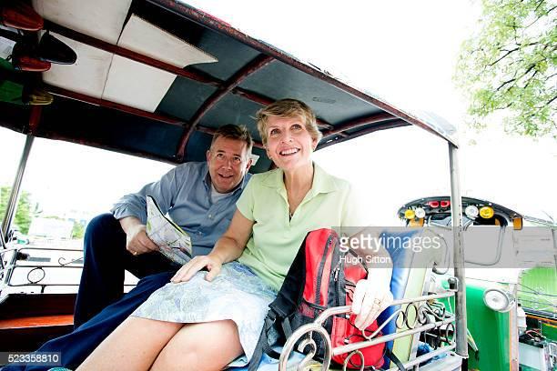 mature couple in rickshaw sightseeing, bangkok, thailand - hugh sitton bildbanksfoton och bilder