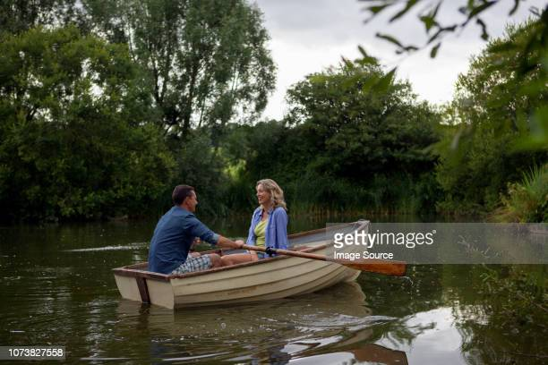 mature couple in rowing boat on rural lake - rowing boat stock pictures, royalty-free photos & images