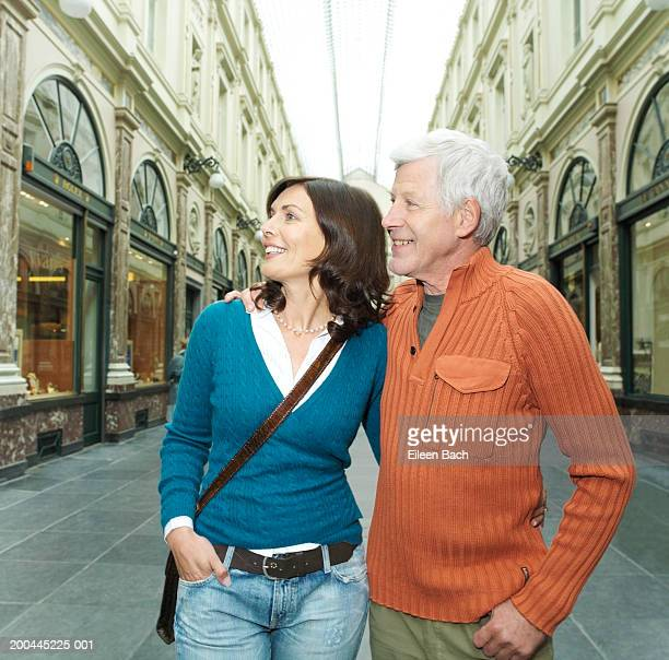 Mature couple in shopping centre, arms around each other