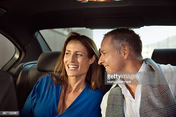 Mature couple in the backseat of a sedan.