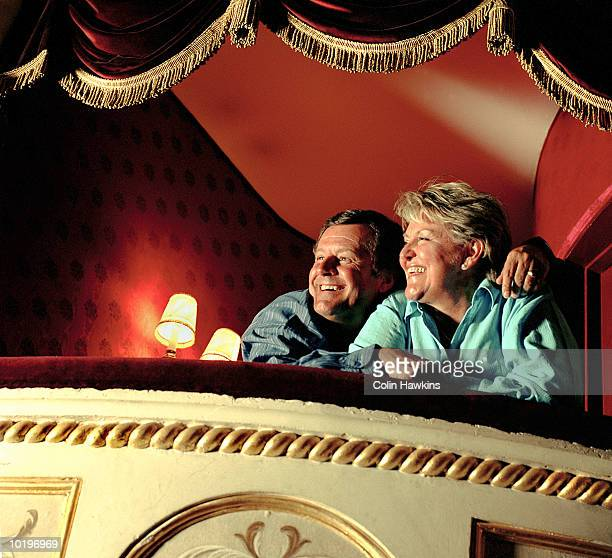 Mature couple in theatre box, laughing
