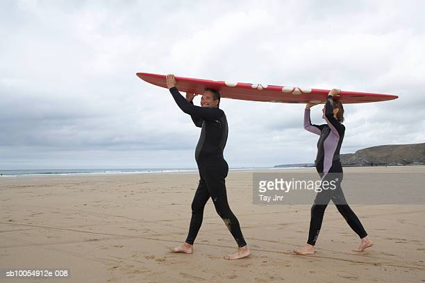 Mature couple in wetsuits carrying surfboard on heads along beach, side view