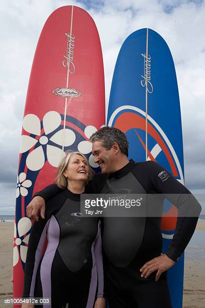 Mature couple in wetsuits, embracing in front of surfboards