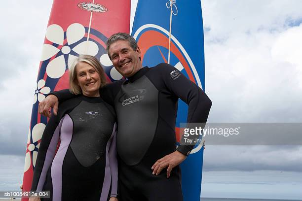 Mature couple in wetsuits, embracing in front of surfboards, portrait