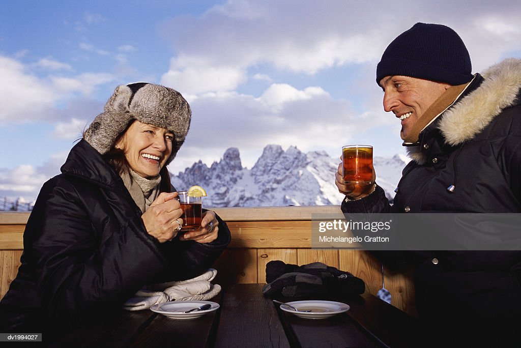 Mature Couple in Winter Clothing Sitting Outdoors at a Table Drinking Tea : Stock Photo