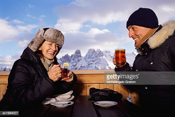 Mature Couple in Winter Clothing Sitting Outdoors at a Table Drinking Tea