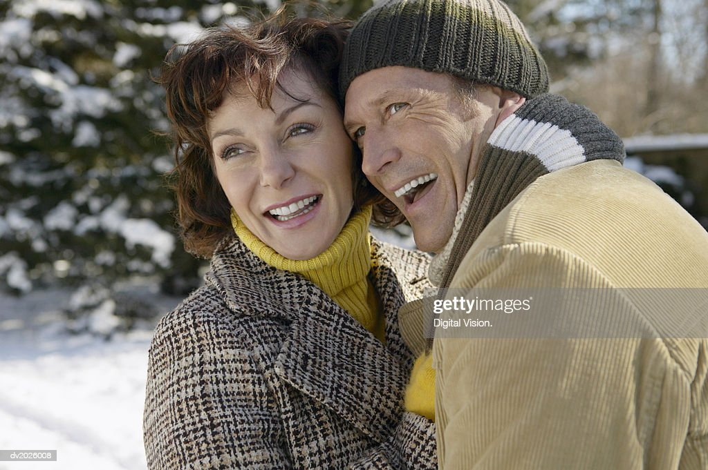 Mature Couple in Winter Clothing Stand Outdoors Embracing : Stock Photo