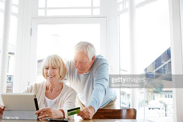 mature couple internet shopping in a cafe - older woman bending over stock pictures, royalty-free photos & images
