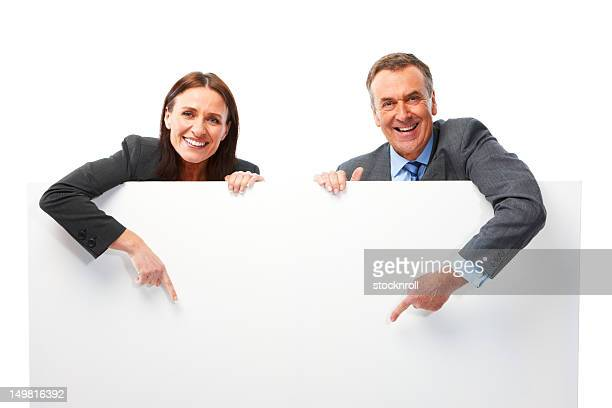 Mature couple isolated on white background pointing at board