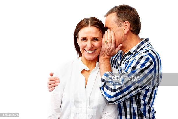 Mature couple isolated on white background whispering
