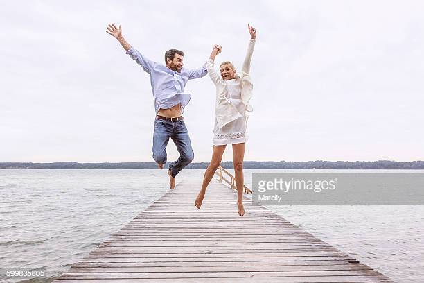Mature couple jumping for joy on pier