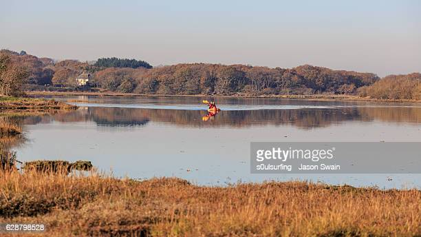 mature couple kayaking at newtown nature reserve on the isle of wight. - s0ulsurfing stock-fotos und bilder