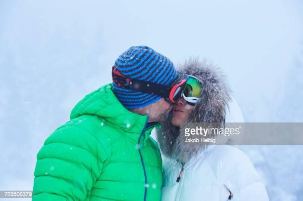 mature couple kissing in falling snow, gstaad, switzerland - 毛皮の飾り ストックフォトと画像