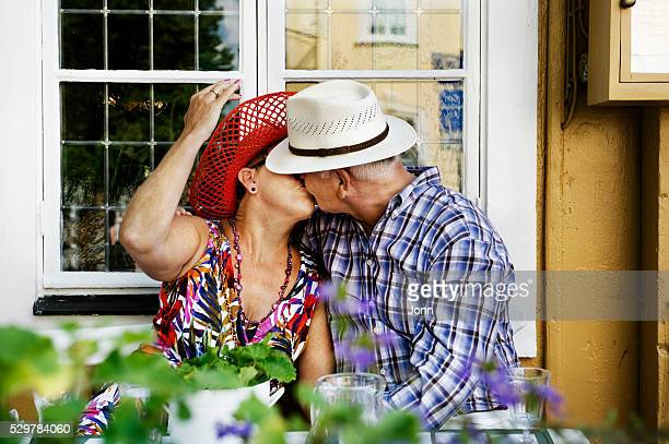 Mature couple kissing in front of window