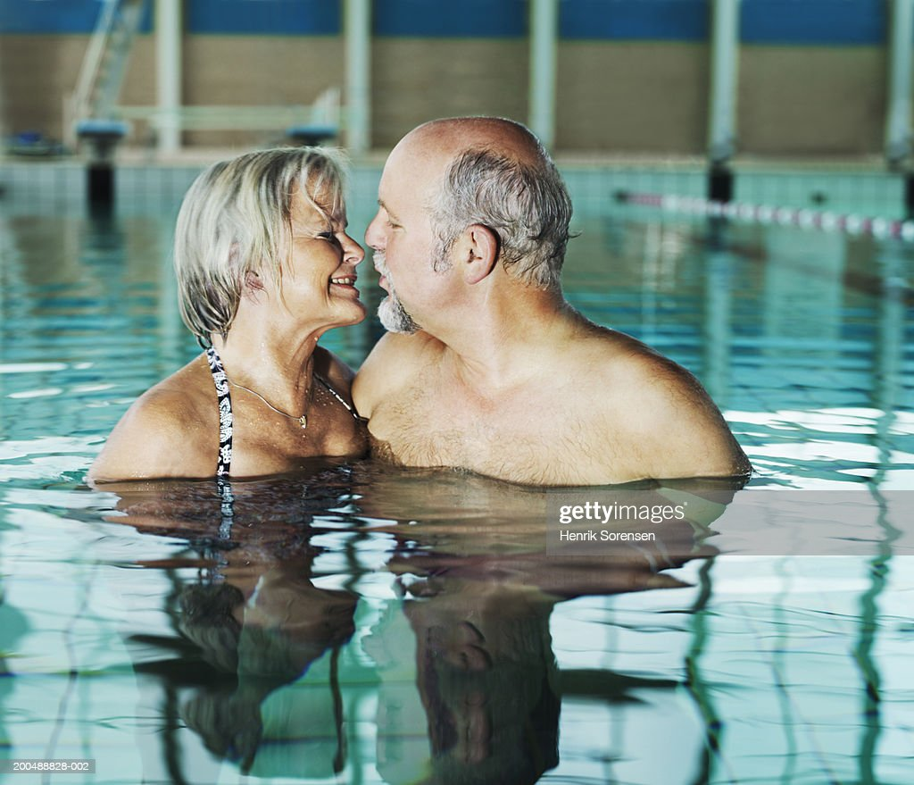 mature couple kissing in swimming pool stock photo | getty images