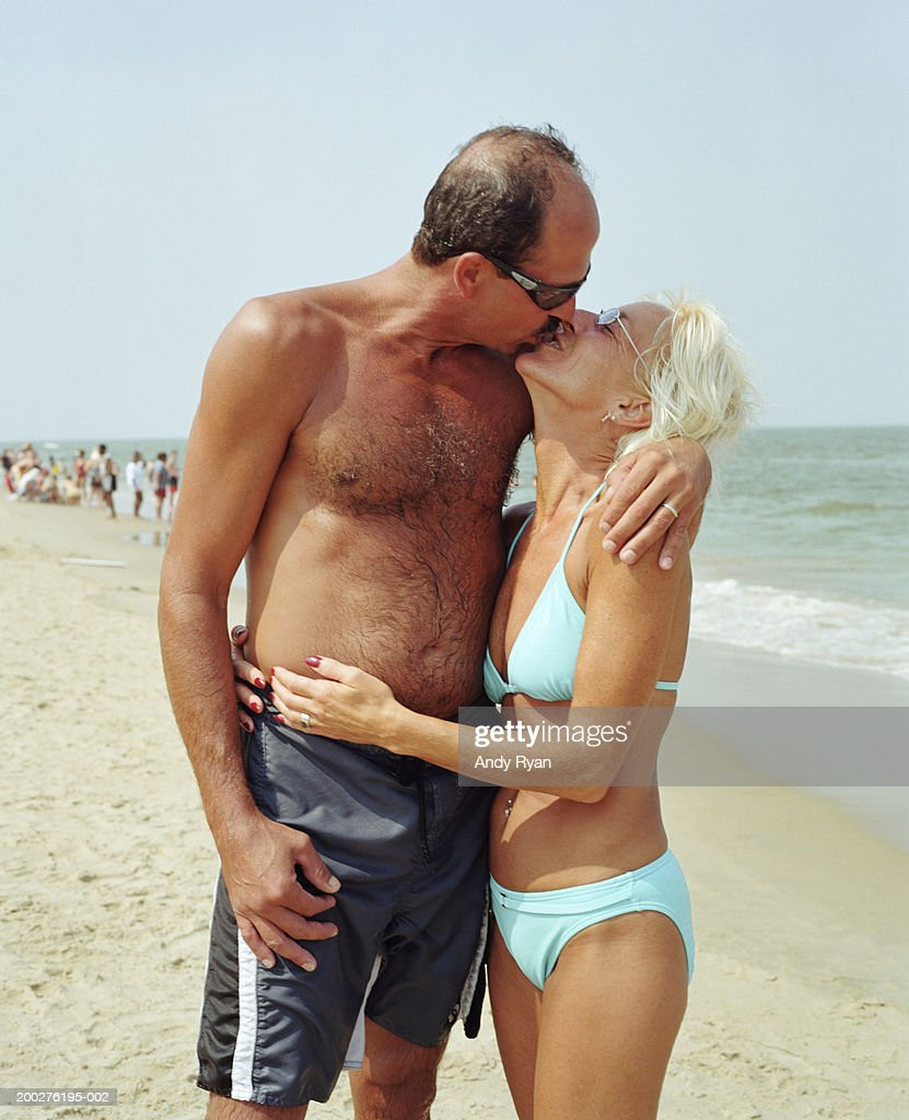 mature couple kissing on beach side view stock photo | getty images