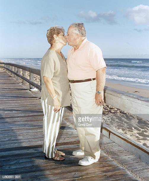 mature couple kissing on boardwalk - fat guy on beach stock pictures, royalty-free photos & images