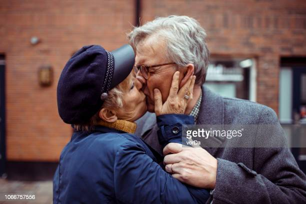 oudere paar zoenen - kiss stockfoto's en -beelden