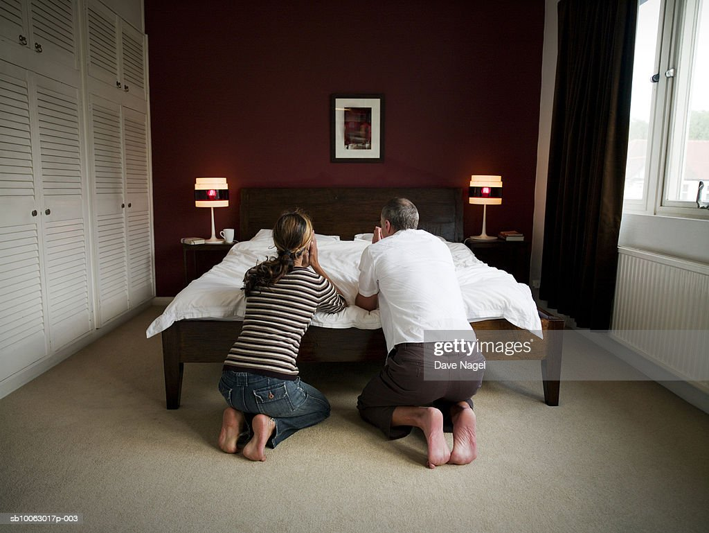 Mature couple kneeling by bed, praying, rear view : Stock Photo