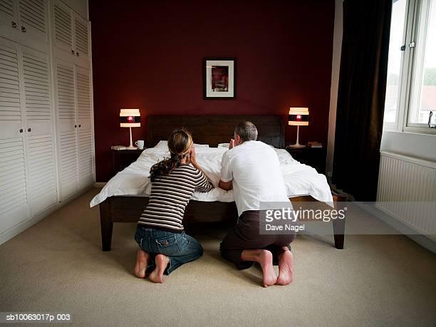 mature couple kneeling by bed, praying, rear view - mulher orando de joelhos imagens e fotografias de stock
