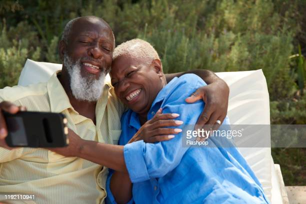Mature couple laugh taking selfies