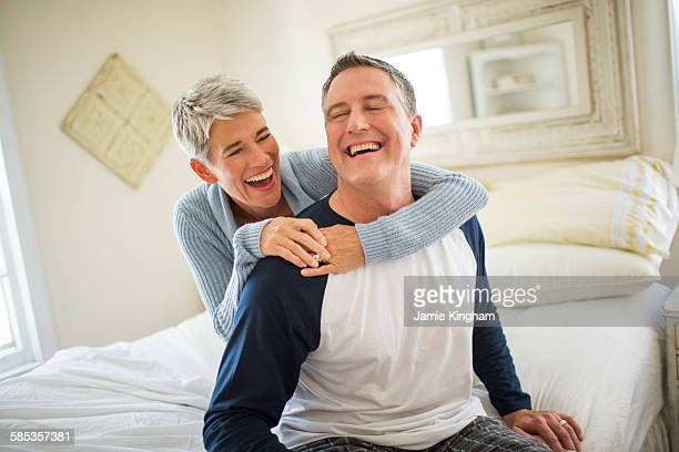 Mature couple laughing and fooling around on bed