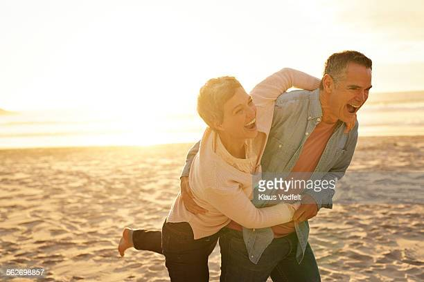 Mature couple laughing & hugging on beach