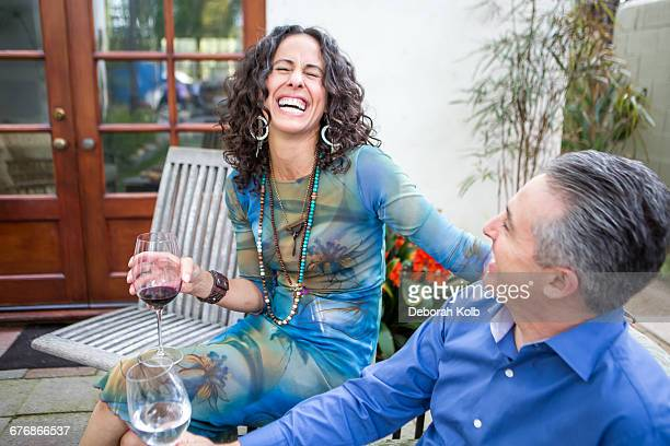 Mature couple laughing on patio at garden party