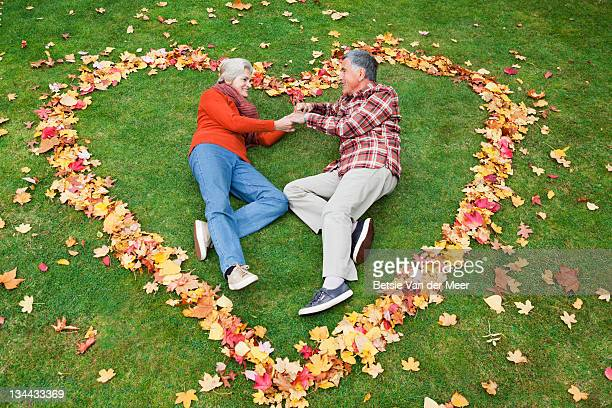 Mature couple laying in heart of autumn leaves.