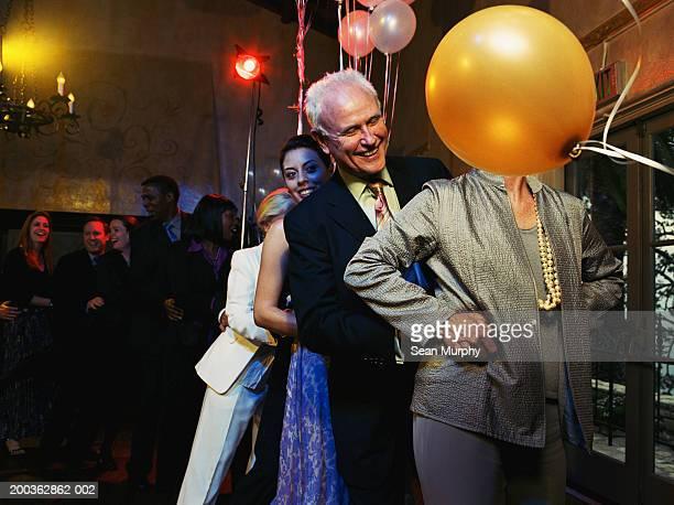 Mature couple leading conga line on dance floor