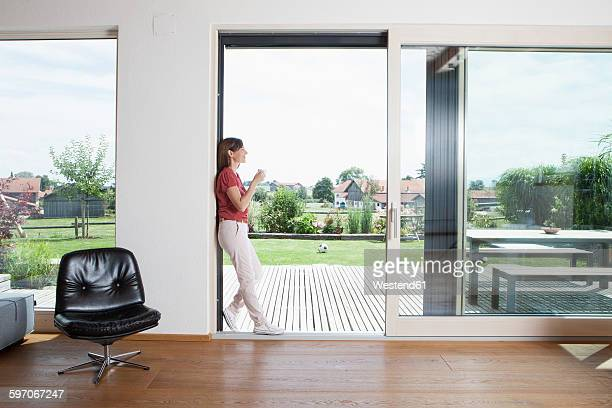 Mature couple leaning in garden door with cup of coffee