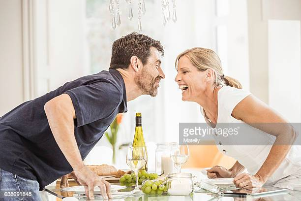 Mature couple leaning over glass table, face to face, laughing