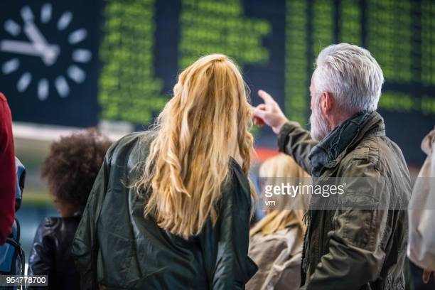 Mature couple looking and poiting at airport timeline board