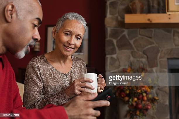 Mature couple looking at cellphone by fireplace