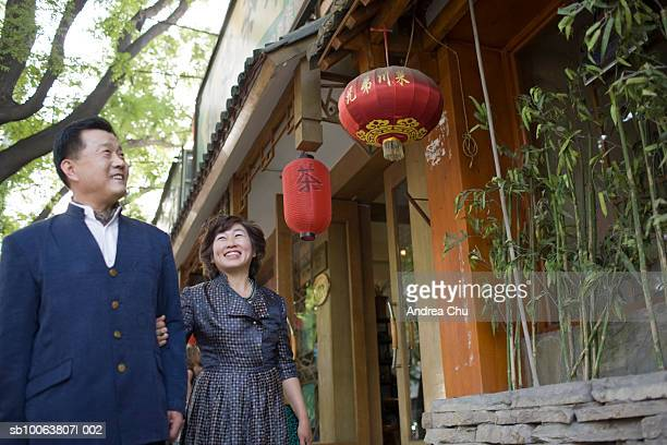 Mature couple looking at Chinese lanterns and smiling, low angle view