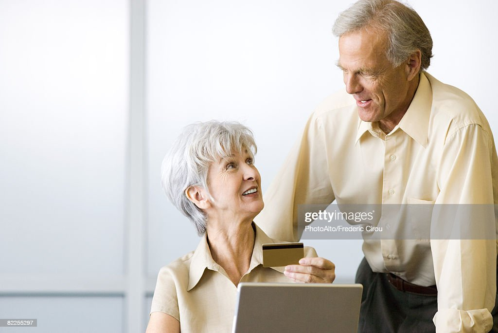 Mature couple looking at each other, woman sitting and holding credit card, man standing : Stock Photo