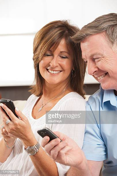 Mature Couple looking at each others mobile phones