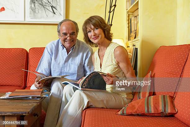 Mature couple looking at holiday brochures, smiling, portrait