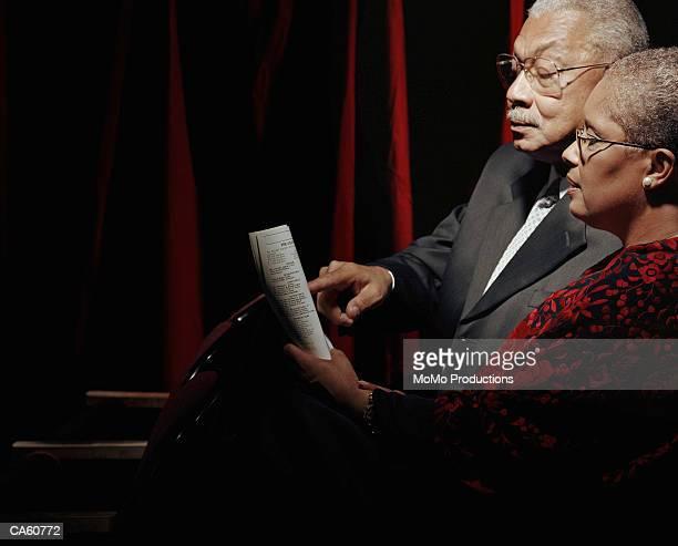 mature couple looking at program in opera house - opernhaus stock-fotos und bilder