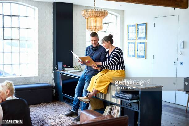 mature couple looking at vinyl record in stylish flat - 50 59 years stock pictures, royalty-free photos & images