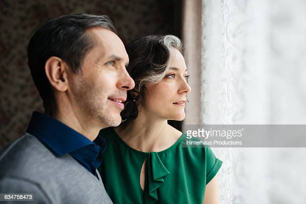 Mature couple looking out of a big window.