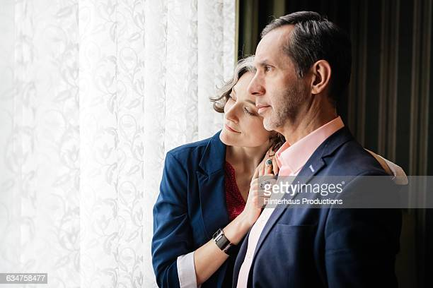 Mature couple looking out of a bright window