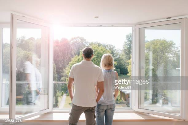 mature couple looking out of window into the sun - investition stock-fotos und bilder