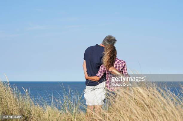 mature couple looking out to sea - seascape stock pictures, royalty-free photos & images