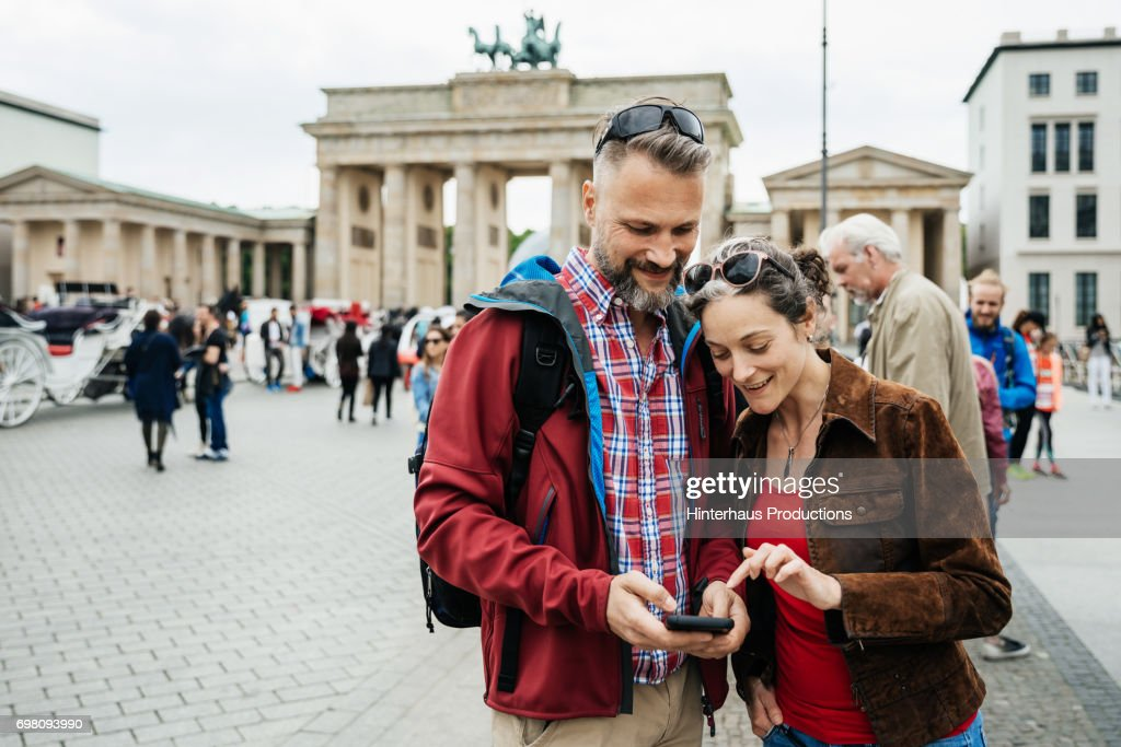 Mature Couple Looking Over Photos They Have Taken At Brandenburg Gate in Berlin : Stock Photo